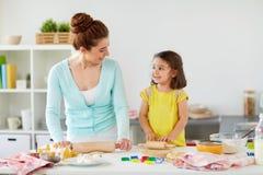 愉快的在家做曲奇饼的母亲和女儿 免版税库存图片