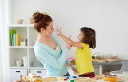 愉快的在家做曲奇饼的母亲和女儿 库存照片