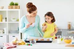 愉快的在家吃曲奇饼的母亲和女儿 库存照片
