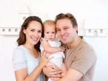 愉快的在家抱着逗人喜爱的婴孩的母亲和父亲 库存图片