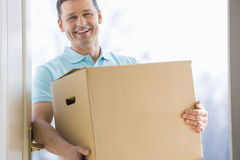 愉快的在新房入口的人运载的纸板箱  图库摄影