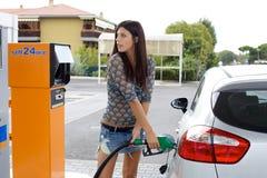 愉快的在汽车的妇女抽的气体 免版税库存照片