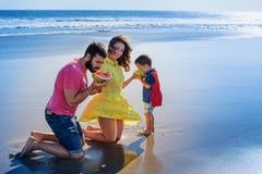 愉快的在沙子海滩的家庭滑稽的野餐与海海浪 免版税库存照片