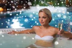 愉快的在游泳池的妇女饮用的香槟 库存图片