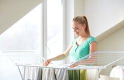 愉快的在烘干机的妇女垂悬的衣裳在家 免版税库存图片