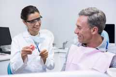 愉快的在牙齿模子的牙医教的人掠过的牙 免版税图库摄影