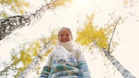 愉快的在秋天公园女服被编织的毛线衣 有快乐和激动的少妇乐趣投掷的黄色离开  股票视频