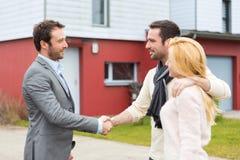 年轻愉快的在签合同以后的夫妇握手房地产开发商 免版税库存照片