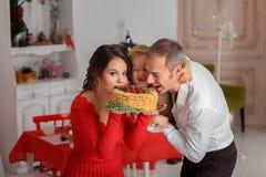 愉快的在背景厨房的家庭叮咬鲜美圣诞节蛋糕 库存照片