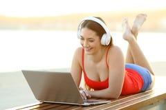 愉快的在膝上型计算机的妇女观看的媒介在海滩 图库摄影