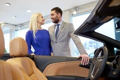 愉快的在车展或沙龙的夫妇买的汽车 库存照片