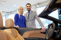 愉快的在车展或沙龙的夫妇买的汽车 库存图片