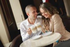 愉快的在都市café的夫妇饮用的咖啡 免版税库存照片