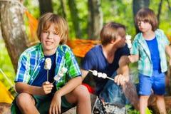 愉快的在露营地的男孩藏品烤shmallows 免版税库存照片