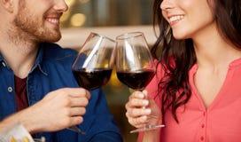 愉快的在餐馆的夫妇饮用的红酒 免版税库存图片