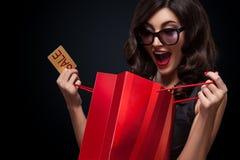 愉快的在黑暗的背景的妇女开放红色袋子在黑星期五假日 免版税库存图片