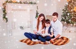 愉快的在Xmas树附近的家庭读书圣诞节童话 假日树和当前礼物盒之前装饰的客厅 免版税库存图片