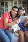 愉快的坐与爱犬和听到音乐的母亲和女儿在耳机 免版税库存图片