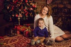 愉快的坐在圣诞树和壁炉附近的母亲和儿子 库存照片