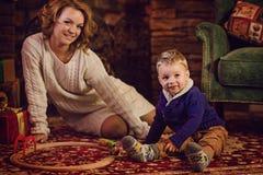 愉快的坐在圣诞树和壁炉附近的母亲和儿子 免版税库存照片