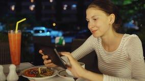 愉快的坐妇女使用智能手机的和的传讯在餐馆在晚上 免版税图库摄影