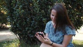 愉快的坐户外在公园的少女妇女深色的夏天,使用有语音识别ai音频的手机 股票视频