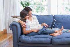 愉快的坐长沙发和使用膝上型计算机的母亲和女儿 免版税图库摄影