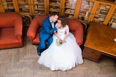 愉快的基于红色沙发的新娘和新郎在老图书馆 库存图片