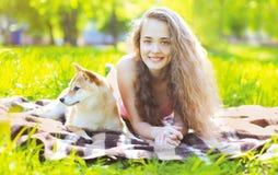 愉快的基于草的女孩和狗 免版税库存图片
