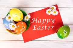 愉快的复活节卡片用鸡蛋和花在木背景 免版税库存图片