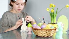 愉快的复活节 一个甜卷曲女孩为复活节的庆祝做准备 她绘兔子的木图 影视素材