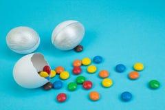 愉快的复活节 与多彩多姿的糖果装饰的残破的复活节彩蛋在蓝色背景 免版税库存图片