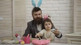 愉快的复活节 爸爸和他的小女儿一起获得乐趣,当为复活节假日做准备时 在桌上是篮子 影视素材