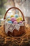 愉快的复活节卡片用在篮子的逗人喜爱的色的鸡蛋与鞋带 库存图片