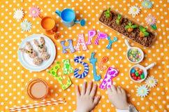 愉快的复活节词用儿童的手和甜点和汁液 库存图片