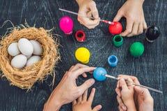 愉快的复活节A绘复活节彩蛋的母亲、父亲和他们的儿子 愉快的家庭为复活节做准备 免版税库存照片