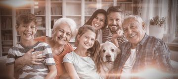 愉快的多一代家庭画象坐沙发在客厅 免版税库存图片