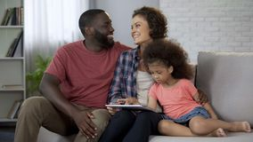 愉快的多种族家庭计划旅行假日,预定在网上在片剂 库存图片