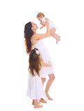 愉快的大家庭!有两个儿童女儿的年轻母亲白色的 免版税库存图片