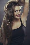 愉快的夫人用手通过长的头发 库存照片