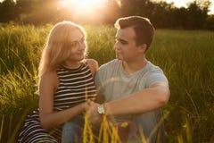 年轻愉快的夫妇一起坐握他们的手的草 图库摄影