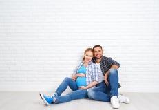 愉快的夫妇丈夫和怀孕的妻子在空白的砖墙附近 图库摄影