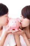 年轻愉快的夫妇亲吻桃红色存钱罐 库存照片