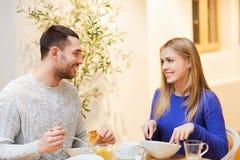 愉快的夫妇会议和有晚餐在咖啡馆 免版税库存图片