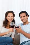 愉快的夫妇使叮当响的杯红葡萄酒 免版税库存照片
