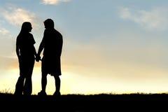 愉快的夫妇剪影握手和谈话在日落 免版税图库摄影