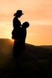 愉快的夫妇剪影有浪漫日落背景 免版税库存照片