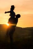 愉快的夫妇剪影有浪漫日落背景 免版税库存图片
