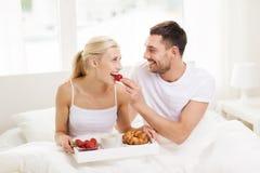 愉快的夫妇吃早餐在床在家 免版税库存图片