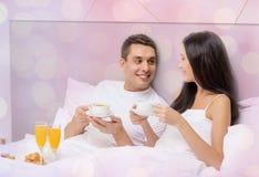 愉快的夫妇吃早餐在床在旅馆 免版税库存照片